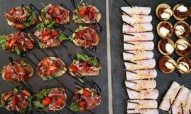 Ορεκτικό των νόστιμων μικρών σάντουιτς με το ζαμπόν, φράουλες και Στοκ Εικόνες