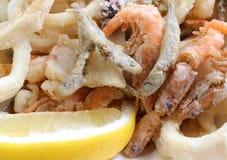 Ορεκτικό υπόβαθρο πολλών τηγανισμένων ψαριών με τις γαρίδες σε ένα τηγάνι στοκ εικόνα