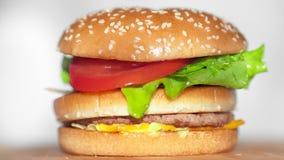 Ορεκτικό φρέσκο κουλούρι με τους σπόρους σουσαμιού για να αφορήσει σαγηνευτικό juicy μεγάλο burger απόθεμα βίντεο