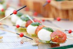 Ορεκτικό, Caprese Ντομάτες, μοτσαρέλα και βασιλικός κερασιών στα οβελίδια Σάλτσα Pesto Νόστιμος πίνακας μπουφέδων Θερινό κόμμα στοκ φωτογραφίες με δικαίωμα ελεύθερης χρήσης