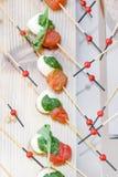 Ορεκτικό, Caprese Ντομάτες, μοτσαρέλα και βασιλικός κερασιών στα οβελίδια Σάλτσα Pesto Νόστιμος πίνακας μπουφέδων Θερινό κόμμα στοκ εικόνες