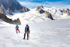 Ορεσίβιοι αλπινιστών ζεύγους που περπατούν τις κλίσεις παγετώνων MONT BLANC στοκ εικόνα με δικαίωμα ελεύθερης χρήσης
