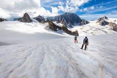 Ορεσίβιοι αλπινιστών ζεύγους που περπατούν τις κλίσεις παγετώνων MONT BLANC στοκ φωτογραφία