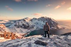 Ορεσίβιος ατόμων που στέκεται στο χιονώδες βουνό στο ηλιοβασίλεμα στοκ εικόνες