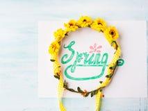 Ορθογραφία λέξης άνοιξη με εγγραφή χεριών και ζώνη στεφανιών λουλουδιών Στοκ Εικόνες