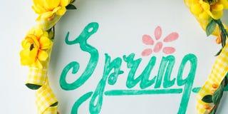Ορθογραφία λέξης άνοιξη με εγγραφή χεριών και ζώνη στεφανιών λουλουδιών Στοκ Φωτογραφία
