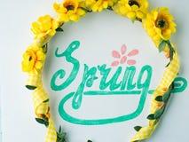 Ορθογραφία λέξης άνοιξη με εγγραφή χεριών και ζώνη στεφανιών λουλουδιών Στοκ φωτογραφίες με δικαίωμα ελεύθερης χρήσης