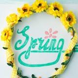 Ορθογραφία λέξης άνοιξη με εγγραφή χεριών και ζώνη στεφανιών λουλουδιών Στοκ φωτογραφία με δικαίωμα ελεύθερης χρήσης