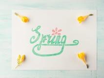 Ορθογραφία λέξης άνοιξη με εγγραφή χεριών και κίτρινα λουλούδια Στοκ Φωτογραφίες