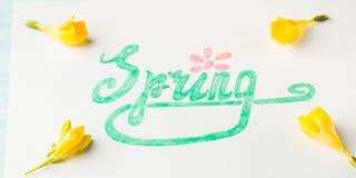 Ορθογραφία λέξης άνοιξη με εγγραφή χεριών και κίτρινα λουλούδια Στοκ εικόνες με δικαίωμα ελεύθερης χρήσης