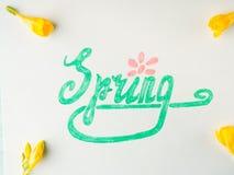 Ορθογραφία λέξης άνοιξη με εγγραφή χεριών και κίτρινα λουλούδια Στοκ Φωτογραφία