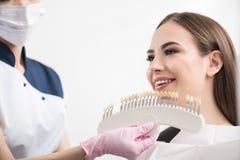 Ορθοδοντικός που επιλέγει την οδοντική κορώνα στην εξερχόμενη γυναίκα Στοκ Εικόνες