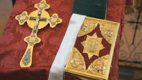 Ορθόδοξοι σταυρός και Βίβλος στο χρυσό πλαίσιο κλείστε επάνω φιλμ μικρού μήκους