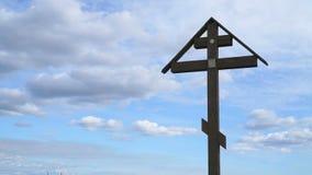 Ορθόδοξος σταυρός σε ένα υπόβαθρο των επιπλεόντων σύννεφων απόθεμα βίντεο