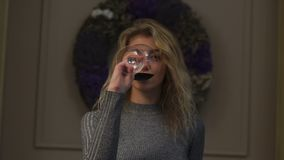 Οριζόντια άποψη του αρκετά ξανθού κρασιού κατανάλωσης κοριτσιών στο υπόβαθρο του στεφανιού Χριστουγέννων φιλμ μικρού μήκους