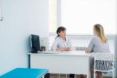 Οριζόντια άποψη του ευτυχούς ασθενή στο γραφείο γιατρών ` s στοκ φωτογραφία
