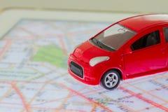 Οριζόντια φωτογραφία του κόκκινου παιχνιδιού αυτοκινήτων κινηματογραφήσεων σε πρώτο πλάνο στο χάρτη σε SCR ταμπλετών Στοκ Φωτογραφίες