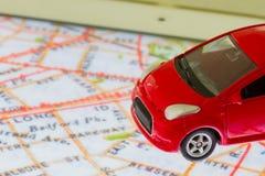 Οριζόντια φωτογραφία του κόκκινου παιχνιδιού αυτοκινήτων κινηματογραφήσεων σε πρώτο πλάνο στο χάρτη σε SCR ταμπλετών Στοκ Εικόνα