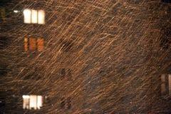Οριζόντια φωτογραφία του χρυσού χιονιού το χειμερινό βράδυ, το φως από το φανάρι και τα παράθυρα στοκ εικόνες