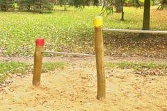 Οριζόντιοι φραγμοί χάλυβα στους ξύλινους στυλοβάτες στην παιδική χαρά παιδιών Πορτοκαλιά άμμος κάτω από τους φραγμούς, πράσινο πά Στοκ Φωτογραφία