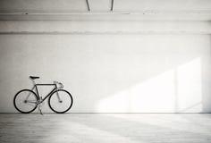 Οριζόντιος κενός βρώμικος ομαλός γυμνός συμπαγής τοίχος φωτογραφιών στο σύγχρονο στούντιο ανοιχτού χώρου με το κλασικό ποδήλατο Μ ελεύθερη απεικόνιση δικαιώματος