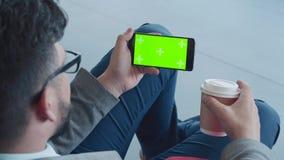 Οριζόντιος προσανατολισμός Smartphone με μια πράσινη οθόνη στα χέρια ατόμων ` s φιλμ μικρού μήκους
