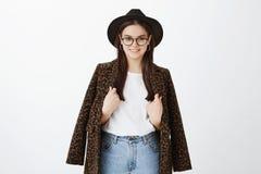 Οριζόντιος πυροβολισμός της μοντέρνης θηλυκής μόδας blogger στο καθιερώνοντα τη μόδα καπέλο, τα γυαλιά και το παλτό με την τυπωμέ στοκ φωτογραφία