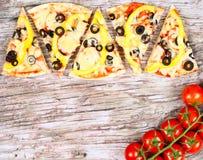 Οριζόντιο έμβλημα τροφίμων με τα κομμάτια των σπιτικών ντοματών κερασιών πιτσών κόκκινων στο ξύλινο υπόβαθρο Κενό διάστημα για το Στοκ φωτογραφίες με δικαίωμα ελεύθερης χρήσης