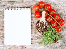 Οριζόντιο έμβλημα τροφίμων με τις ντομάτες, το arugula, peppercorns και το σημειωματάριο κερασιών στο ξύλινο υπόβαθρο Κενό διάστη Στοκ Εικόνες