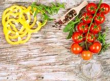 Οριζόντιο έμβλημα τροφίμων με τις ντομάτες κερασιών, την κίτρινη πάπρικα, το arugula και peppercorns στο ξύλινο υπόβαθρο Κενό διά Στοκ εικόνες με δικαίωμα ελεύθερης χρήσης