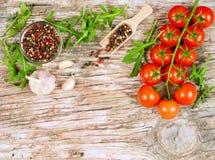 Οριζόντιο έμβλημα τροφίμων με τις ντομάτες κερασιών, το φρέσκο arugula, το σκόρδο και peppercorns στο ξύλινο υπόβαθρο Κενό διάστη Στοκ Εικόνα