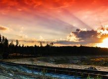 Οριζόντιο κόκκινο ζωηρό ηλιοβασίλεμα στο εκλεκτής ποιότητας τοπίο διαδρομής σιδηροδρόμου Στοκ Φωτογραφίες