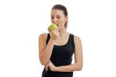 Οριζόντιο πορτρέτο ενός νέου κοριτσιού σε μια μαύρη μπλούζα που τρώει τη Apple Στοκ Εικόνες