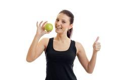 Οριζόντιο πορτρέτο του νέου λεπτού κοριτσιού σε μια μαύρη μπλούζα που κρατά στο χέρι της την πράσινη Apple και παρουσιάζει κατηγο Στοκ φωτογραφία με δικαίωμα ελεύθερης χρήσης