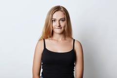 Οριζόντιο πορτρέτο του όμορφου νέου θηλυκού με την ξανθή τρίχα, τα μπλε μάτια και το υγιές δέρμα, που δαγκώνουν το χαμηλότερο χεί Στοκ εικόνα με δικαίωμα ελεύθερης χρήσης