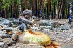 ορυκτό ύδωρ πηγής Ροές του νερού από τη μορφή αριθμών του αγοριού με την κανάτα Arshan Ρωσία Στοκ Εικόνες
