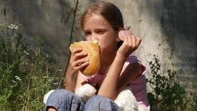 Ορφανό λυπημένο παιδί στο εγκαταλειμμένο σπίτι, δυστυχισμένο περιπλανώμενο κορίτσι που τρώει το ψωμί, λουκάνικο 4K απόθεμα βίντεο