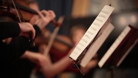 Ορχήστρα αιθουσών Άνθρωποι που υπερασπίζονται και που παίζουν τα βιολιά τις σημειώσεις απόθεμα βίντεο