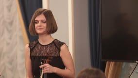 Ορχήστρα αιθουσών Ένας νέος βιολιστής γυναικών υποκύπτει μετά από τη μουσική απόδοση απόθεμα βίντεο