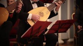 Ορχήστρα αιθουσών Ένα λαγούτο παιχνιδιού ατόμων σε μια μουσική απόδοση φιλμ μικρού μήκους