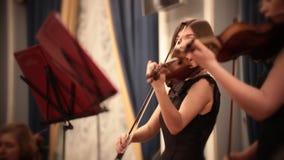 Ορχήστρα αιθουσών Ένα νέο βιολί παιχνιδιού γυναικών κατά τη διάρκεια μιας μουσικής απόδοσης απόθεμα βίντεο