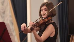 Ορχήστρα αιθουσών Ένα νέο βιολί παιχνιδιού γυναικών κατά τη διάρκεια μιας απόδοσης απόθεμα βίντεο