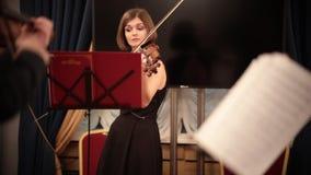 Ορχήστρα αιθουσών Ένα νέο όμορφο βιολί παιχνιδιού γυναικών κατά τη διάρκεια μιας απόδοσης απόθεμα βίντεο