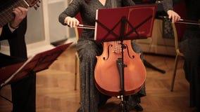 Ορχήστρα αιθουσών Μια γυναίκα στο μακρύ βιολοντσέλο παιχνιδιού φορεμάτων απόθεμα βίντεο