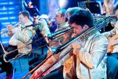 Ορχήστρα με τα μουσικούς όργανα και τους εκτελεστές κατά τη διάρκεια της απόδοσης Στοκ εικόνα με δικαίωμα ελεύθερης χρήσης