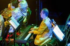 Ορχήστρα με τα μουσικούς όργανα και τους εκτελεστές κατά τη διάρκεια της απόδοσης Στοκ Εικόνες