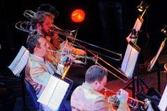 Ορχήστρα με τα μουσικούς όργανα και τους εκτελεστές κατά τη διάρκεια της απόδοσης Στοκ Φωτογραφία