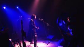 Ορχήστρα ροκ Kukryniksy που αποδίδει στο στάδιο του νυχτερινού κέντρου διασκέδασης Μπλε επίκεντρα μουσικοί Χορός Soloist απόθεμα βίντεο