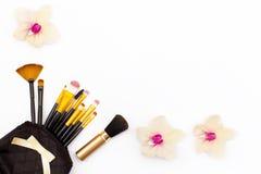 Ορχιδέα βουρτσών Makeup και λίγων λουλουδιών σε ένα άσπρο υπόβαθρο Έννοια της ομορφιάς Επίπεδος βάλτε Στοκ εικόνες με δικαίωμα ελεύθερης χρήσης
