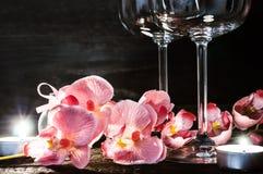 Ορχιδέες και κεριά γυαλιών κρασιού για ένα ρομαντικό βράδυ Στοκ Φωτογραφία
